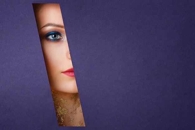 美しい女性の目は紙の穴、明るいメイクアップに見えます。