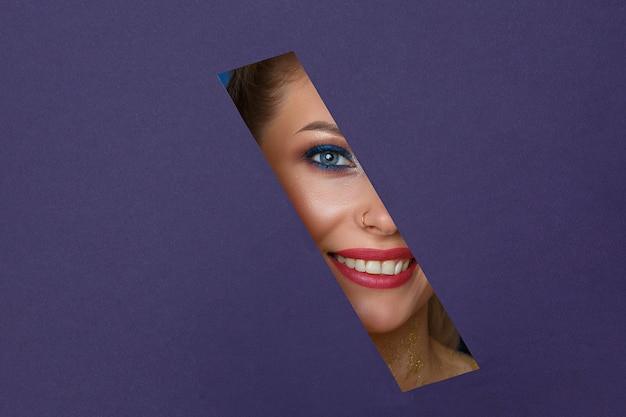Красивые женские глаза смотрят в бумажную дырочку, яркий макияж.