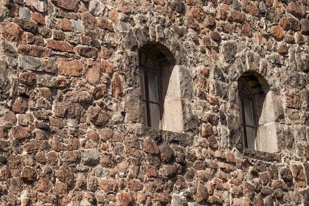 В старой каменной стене есть два окна
