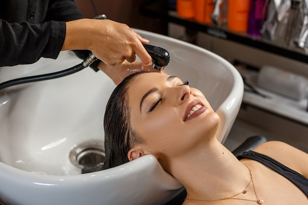洗浄手順美容室で頭を洗う美容師と美しい若い女性。