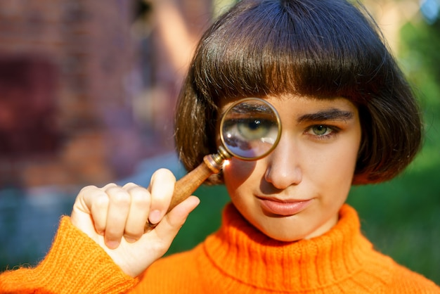 彼女の手に虫眼鏡を持つ自然の中でかわいい女の子、