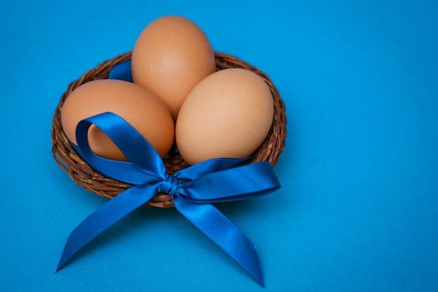 Куриные яйца в соломенной миске с синим бантом на синем фоне,