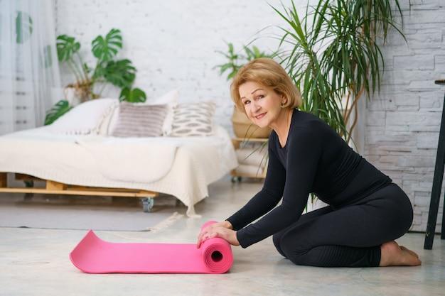 成熟した女性が自宅でのトレーニング後にマットを巻き戻し