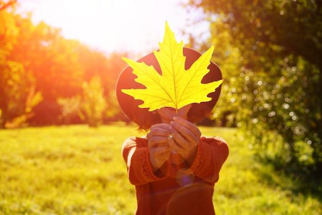 Счастливая женщина в осеннем парке в шляпе с кленовым листом на солнце