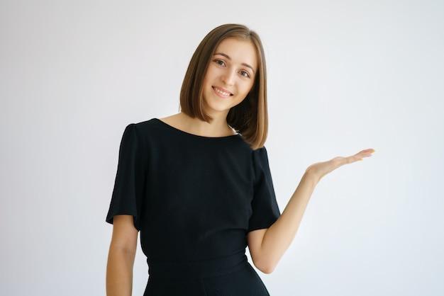 Портрет счастливой милой женщины в черном платье на белом фоне, улыбаясь и показывая жест рукой в сторону, концепция