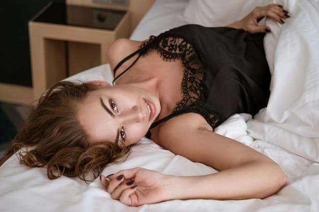 美しいブルネットは黒いスリップでベッドに横たわっています。