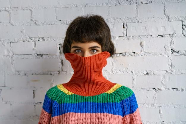 セーターで顔を覆っている色とりどりのセーターの若い女性の肖像画。恥ずかしさの概念