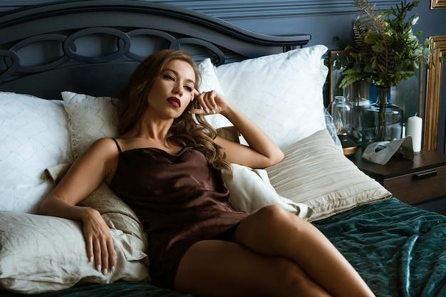 Красивая брюнетка лежит на кровати, темное фото