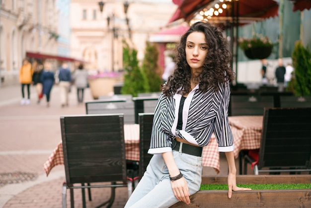 カフェで路上の女性。暗い巻き毛の茶色の目。後ろにテーブルと椅子があります