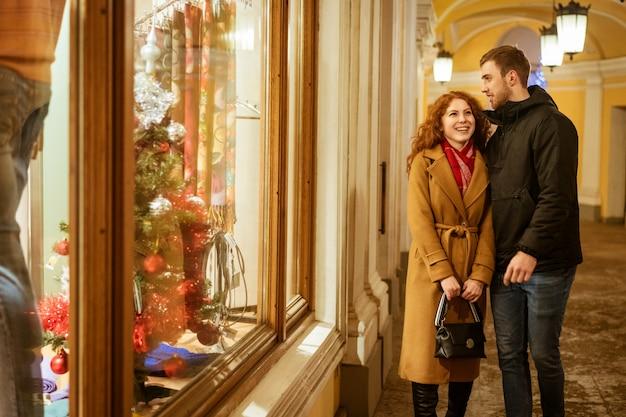 幸せなカップルが夕方に窓を見て通りに立つ