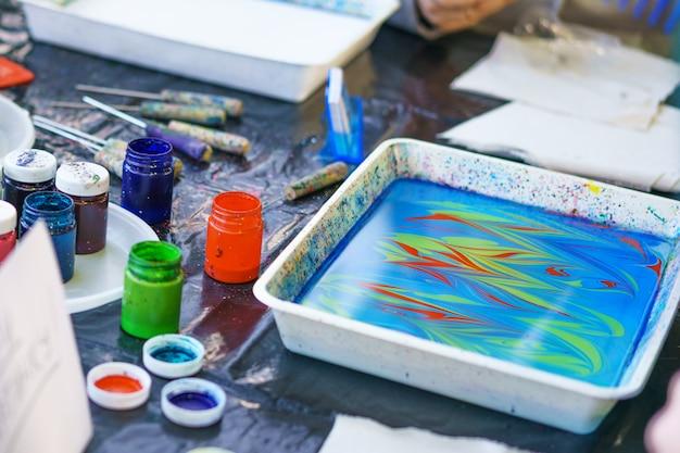 子供は顔なしで水に絵を描く