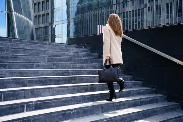 彼女の手にバッグを持つコートを着たビジネスウーマンは、建物への階段を上ります。キャリアとビジネスの概念