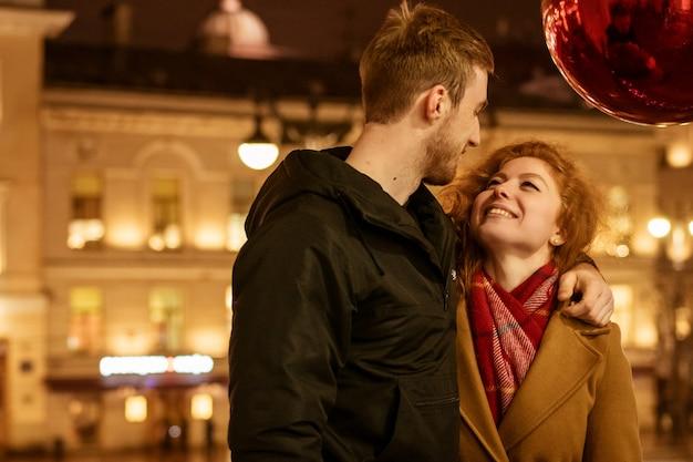 幸せなカップルがお祝いの明かりで夕方に路上の抱擁に立っています。