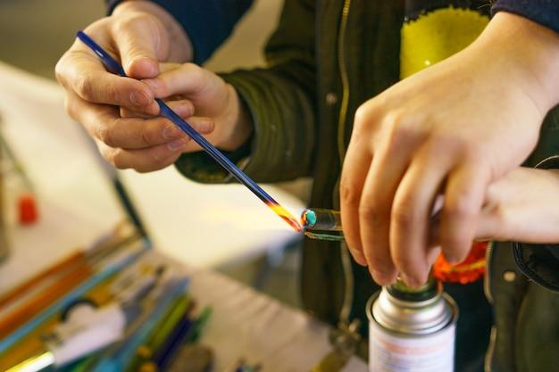 ガラスで装飾的なおもちゃを作ることについてのマスタークラスである先生は、溶けて作る方法を示します。クローズアップとソフトフォーカス