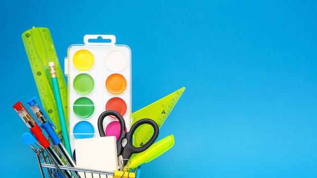 青色の背景におもちゃのショッピングカートの文房具。学年の初めの準備のコンセプト。コピースペース