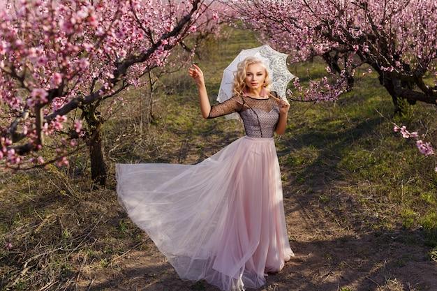 Красивый портрет женщины в саду цветущих персиков