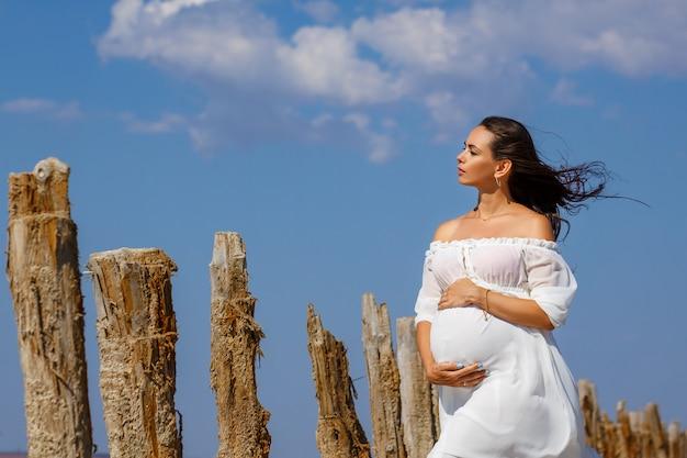 Красивая молодая беременная женщина, стоя в природе на соленое озеро.