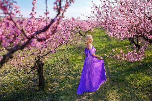 Красивый портрет девушки в весеннем цветущем саду, солнечный день, персиковый сад