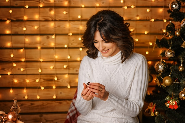 白いセーターのクリスマスツリーの近くの美しい若い女性