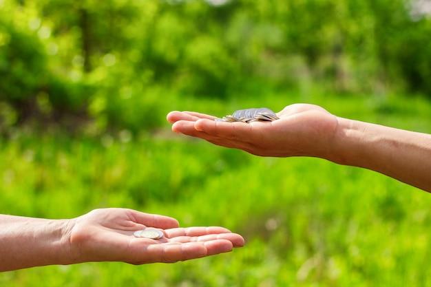 Рука об руку дает монетки на зеленой предпосылке, концепции финансов и займах.
