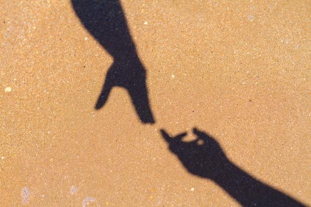 男性の手が砂の背景に女性の手の影に達する