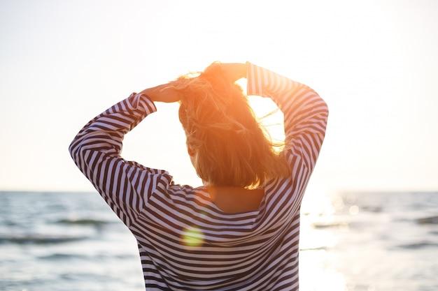 太陽のクローズアップで海を見て立っている女性