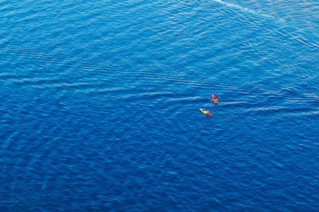 Люди каякинг в синем море вид сверху