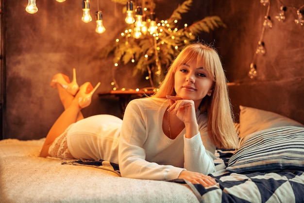 美しい若い女性がベッドの上でポーズ