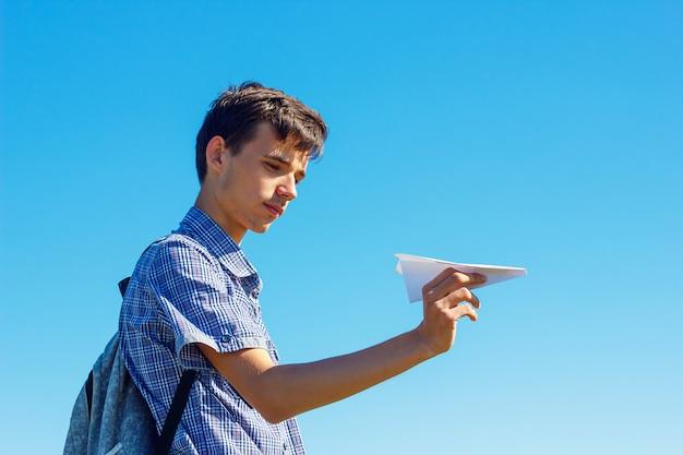Молодой человек на голубом небе держит бумажный самолетик