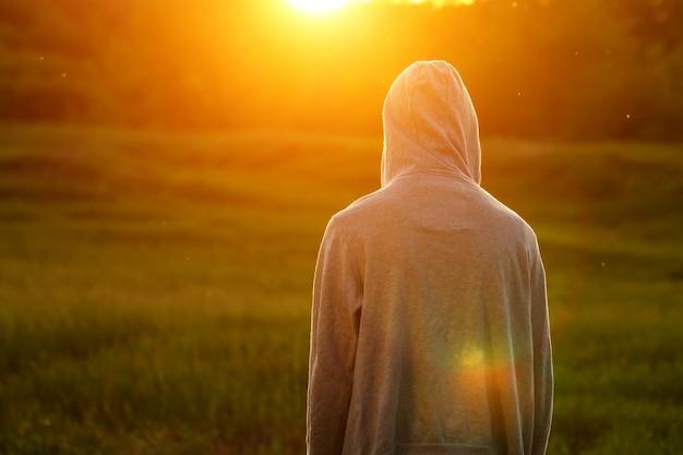Человек в свете заката с поднятыми руками