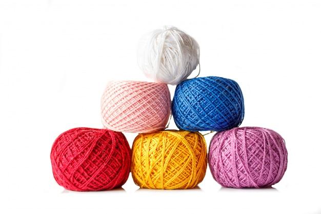 白い背景に編むことのための着色された糸のもつれ。
