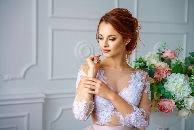 美しい繊細なドレスの美しい赤毛の若い女性の肖像画。