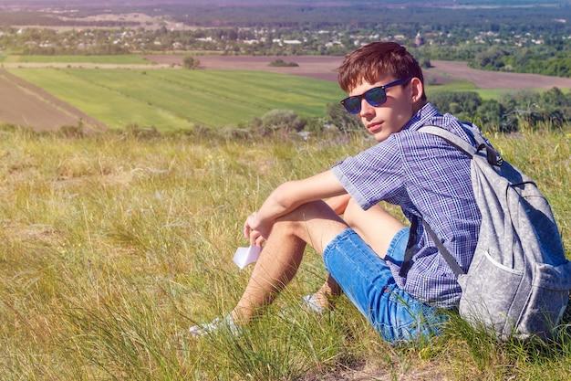 バックパックで座っていると美しい景色、観光の概念を見て若い男