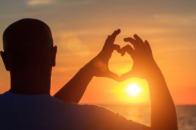 夕焼け空の日光に対して心臓の形で男性の手