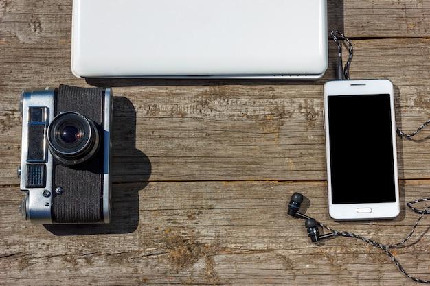 カメラ付き携帯電話とラップトップは木製のテーブルです。