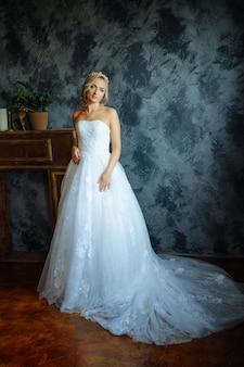電車でとても美しいロングドレスの美しい花嫁が窓のそばに立ちます。