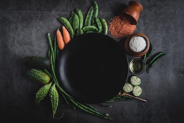 黒いプレートの真ん中の中のメッセージのためのスペースと黒いテーブルの上の野菜