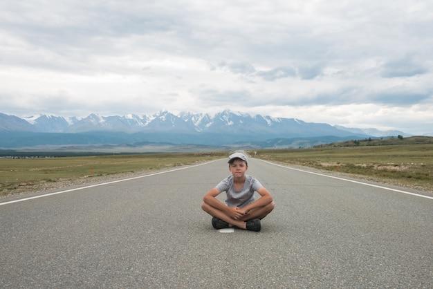 道路上に座っている若い男の子