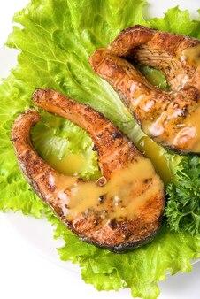 白い背景に分離されたおいしいサケの魚料理
