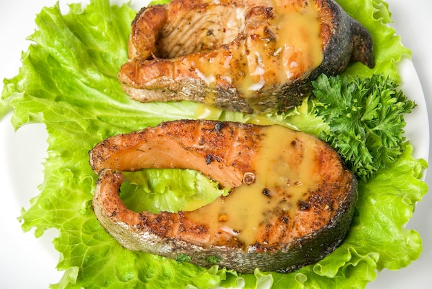 白い背景に分離されたローストチャムサーモンの魚料理