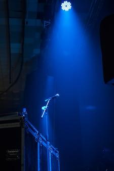 青いライトが付いているコンサートホールのマイク