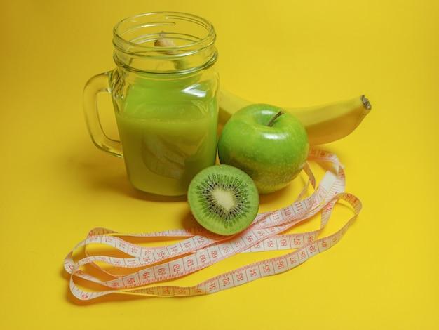 Зеленый здоровый смузи в стеклянной банке: банан, киви, зеленое яблоко. здоровый напиток на желтом фоне.