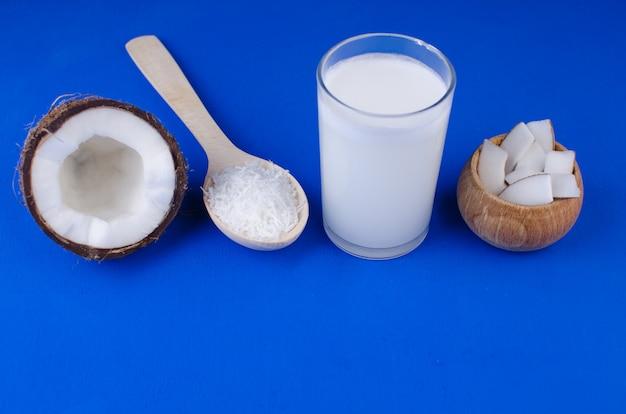 天然のココナッツミルク、ココナッツの削りくず、青色の背景にココナッツチップ。健康食品のコンセプトです。