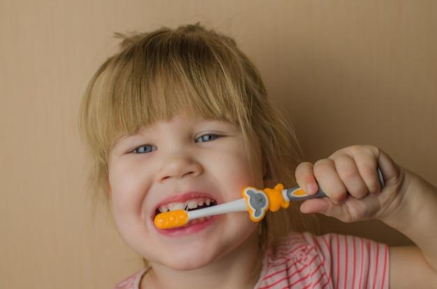 彼女の歯を磨くの幸せな女の子。コピースペース