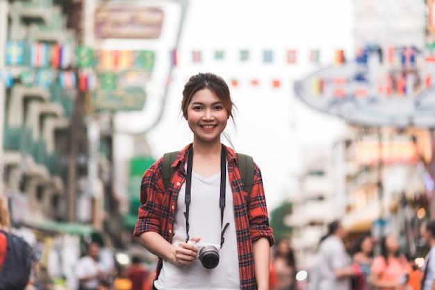 Путешественник турист азиатской женщины путешествуют по дороге кхао сан в бангкоке, таиланд