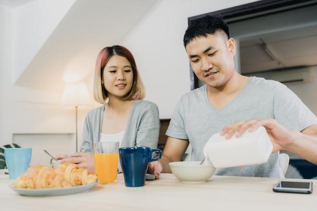 幸せな甘いアジアカップル、朝食、シリアル、牛乳、パン、飲むオレンジジュース