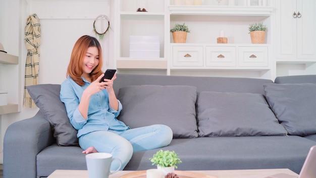 Портрет красивой привлекательной молодой улыбающейся азиатской женщины с помощью смартфона