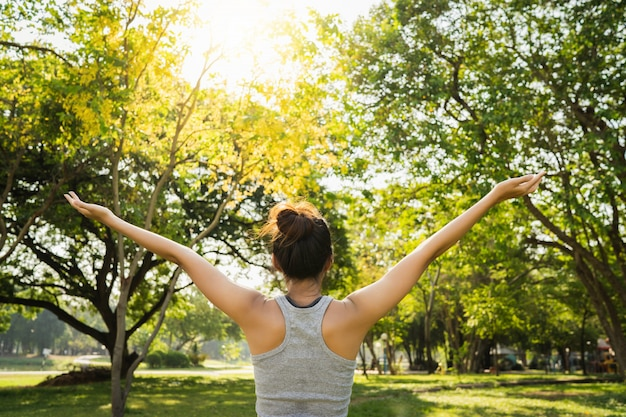 健康的な若いアジアのランナーの女性は運動の前に体をストレッチウォームアップ