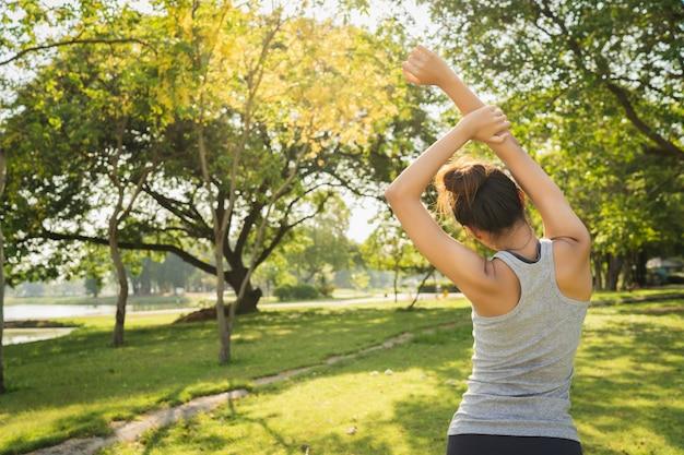 Здоровая молодая азиатская бегунья разминает тело перед тренировкой и йогой