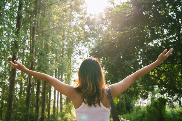 Счастливый молодой азиатский путешественник женщины с рюкзаком идя в лес.
